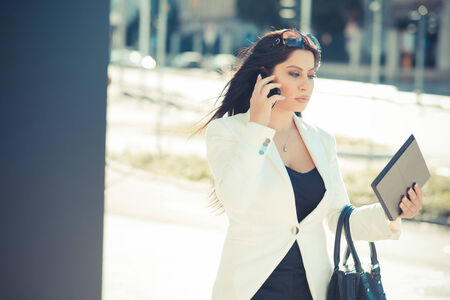 beautiful long black hair elegant business woman using tablet in the city photo