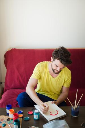 hombre pintando: apuesto inconformista moderna pintura del hombre en casa Foto de archivo