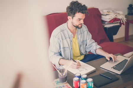 handsome hipster modern man designer working home using laptop at home photo