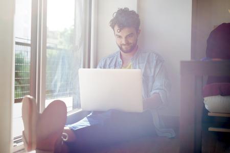 poblíž: pohledný bederní moderní člověk designer pracující doma pomocí přenosného počítače doma