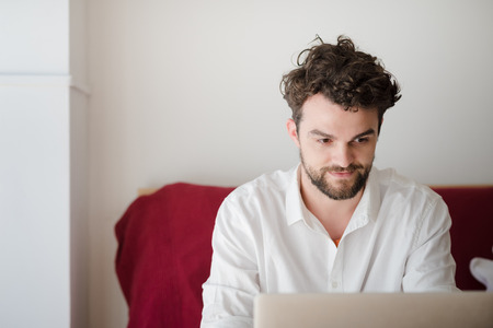 curator: handsome hipster modern man designer working home using laptop at home
