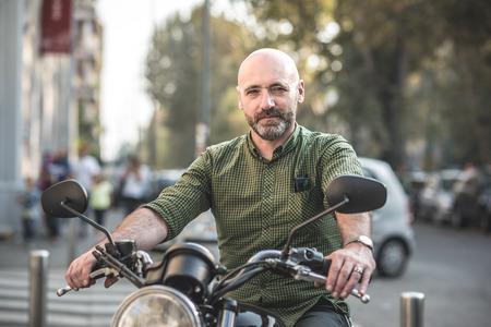 motociclista: apuesto hombre de mediana edad motociclista en la ciudad