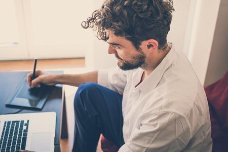 trabajando en casa: apuesto inconformista dise�ador hombre moderno que trabaja a casa usando la computadora port�til en casa