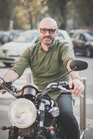 handsome middle aged man motorcyclist in the city photo