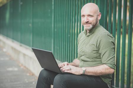 bald man: apuesto hombre de mediana edad que usa el cuaderno en la ciudad Foto de archivo