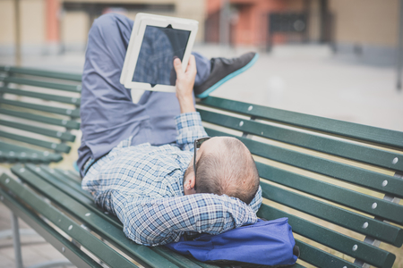 handsome hipster casual multitasking modern man using tablet in the city photo