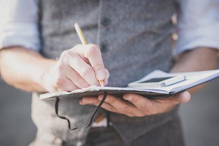 Man writing: close up manos hombre que escribe en el diario y el tel�fono inteligente al aire libre