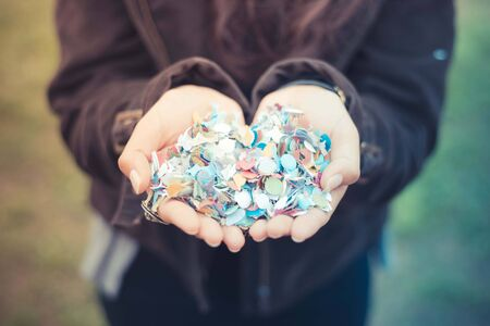 close up of woman hands with confetti outdoor photo