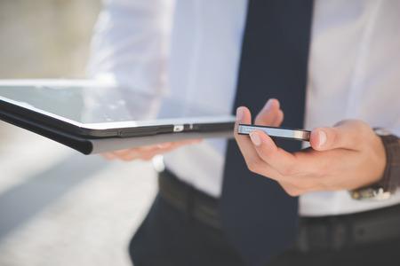 タブレットとスマート フォンのデバイスの屋外を使用するビジネスマンの男の手を閉じる 写真素材