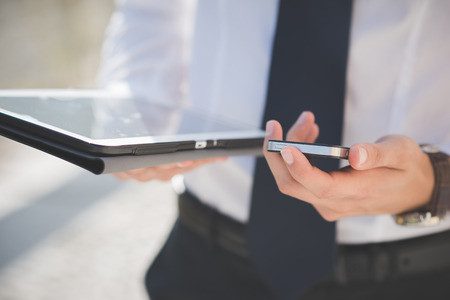 mobile device: close up businessman man hand using tablet and smart phone device outdoor