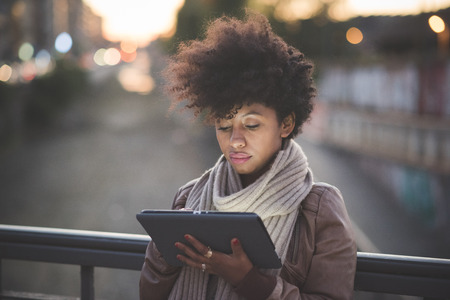 美しい黒い巻き毛のアフリカの女性の夜の町でタブレットを使用して