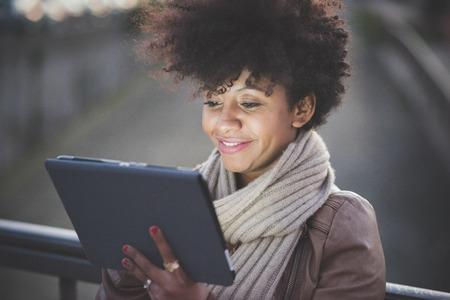 밤 도시에서 태블릿을 사용하여 아름다운 검은 곱슬 머리 흑인 여자