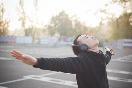 도시 야외 생활에 젊은 미친 재미 아시아 남자 헤드폰으로 음악을 듣고