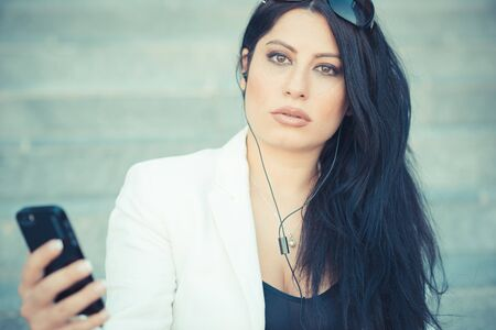 beautiful long black hair elegant business woman using smartphone in the city photo