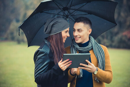 love in rain: young couple in the park during autumn season outdoor - using tablet technological device during raining under umbrella