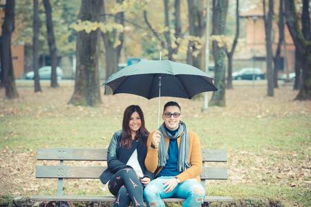 sotto la pioggia: giovane coppia nel parco durante la stagione autunnale all'aperto - gli amanti di San Valentino sotto l'ombrello seduto in una panchina