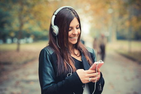 listening device: young beautiful brunette straight hair woman in the park during autumn season - listening to music with headphones and smartphone