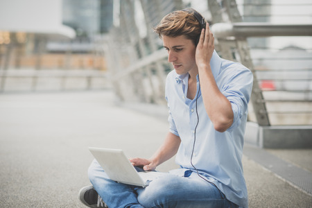 hansome: young model hansome blonde man with notebook and headphones in the city Stock Photo