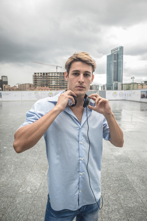 hansome: young model hansome blonde man with music headphones in the city Stock Photo