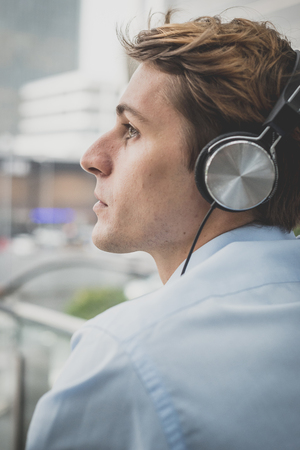 hansome: young model hansome blonde man with headphones in the city Stock Photo
