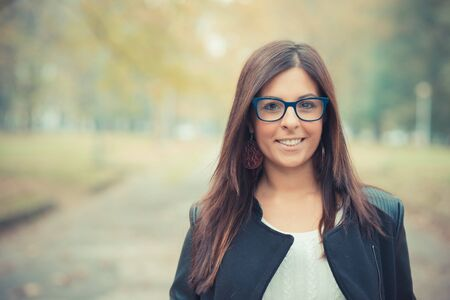 秋のシーズン中に公園で若い美しいブルネット ストレートの髪の女性 写真素材