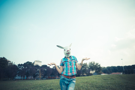 absurd: rabbit mask absurd beautiful young hipster woman in the city Stock Photo