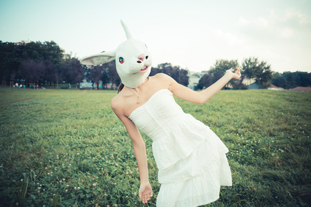 absurd: rabbit mask absurd beautiful young woman with white dress in the city Stock Photo