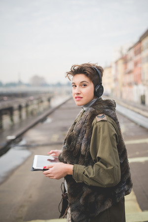 listening device: young beautiful short hair hipster woman in town using tablet technological device connected wireless with headphones listening music