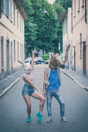 horse and rabbit mask couple of friends young  man and woman in the city Standard-Bild