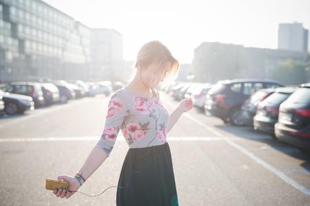 femme blonde: belle jeune femme blonde en plein air dans la rue de la musique d'�coute de la ville et en utilisant smartphone avec �couteurs Banque d'images