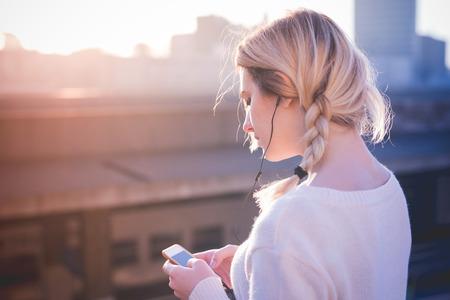 若い美しいブロンドの女性が音楽を聴くイヤホンでスマート フォンを使用して都市の通りの屋外 写真素材