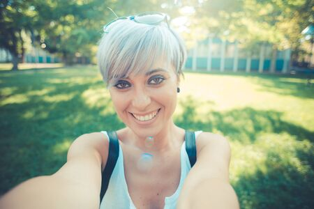 self conceit: young beautiful short blue hair hipster woman selfie in the city