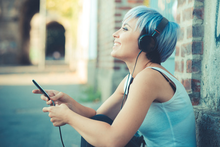 young beautiful short blue hair hipster woman with headphones music in the city Stock Photo - 37120925