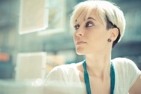 カフェで美しい若い金髪ショートヘア流行に敏感な女性