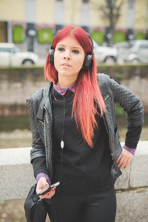 venezuelan: young beautiful red hair venezuelan woman lifestyle in the city of milan outdoor street listening music with headphones Stock Photo