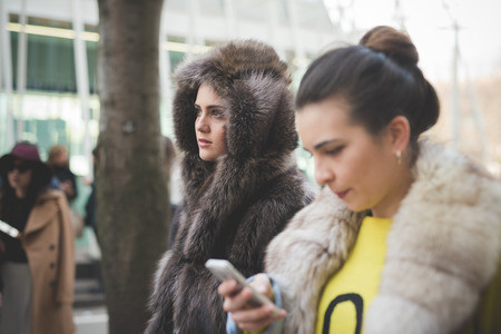 poser: MILAN, ITALY - FEBRUARY 28: People during Milan Fashion week, Italy on February, 28 2015. Eccentric and fashionable people outside city during Milan fashion week wait for models and famous people Editorial
