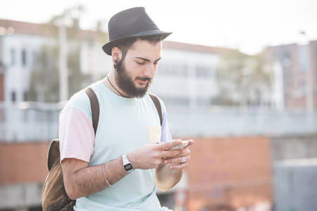 casual men: young handsome hipster modern man using smartphone in town