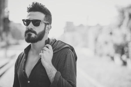 都市の文脈で若いハンサムな魅力的なひげを生やしたモデル男