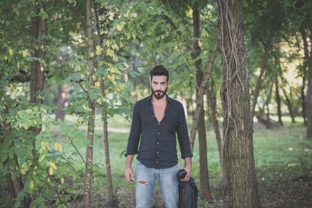 appealing attractive: young handsome attractive bearded model man in the woods