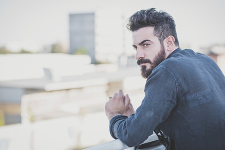contemplative: young handsome attractive bearded model man in urban context Stock Photo