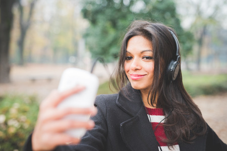 young beautiful indian woman at the park in autumn listening music with headphones Stock Photo