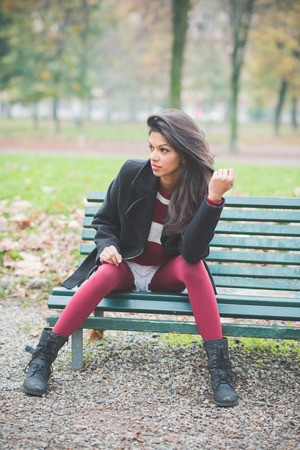 indian style sitting: young beautiful indian woman at the park in autumn