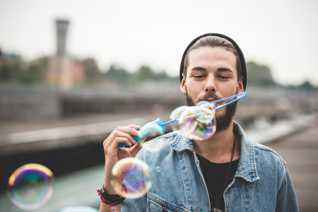 young handsome bearded hipster man blowing bubbles soap in the city Reklamní fotografie - 37418743