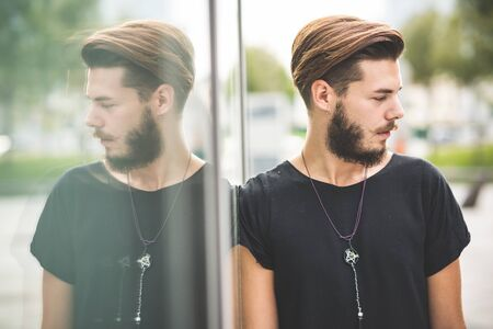 italian people: young handsome bearded hipster man in the city