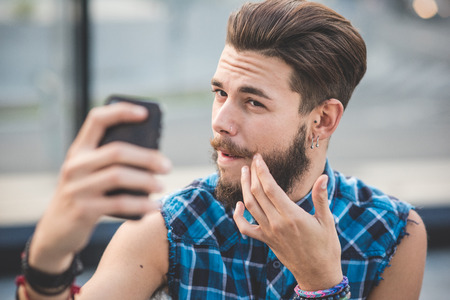 young handsome bearded hipster man selfie in the city Stock Photo