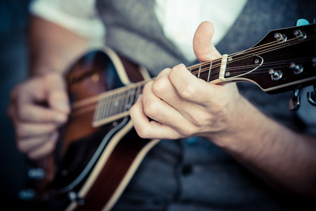 close up hands hipster man playing mandolin in the city