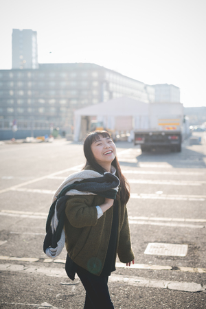 city living: young beautiful asian hipster woman in the city - living town during sunset in backlit - smiling happy having fun with scarf Stock Photo