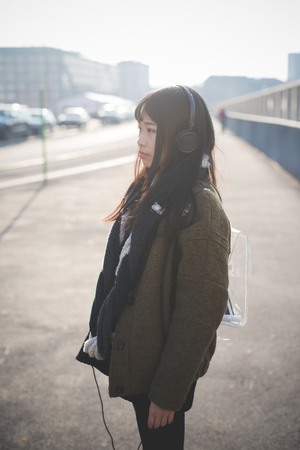 city living: young beautiful asian hipster woman in the city - living town during sunset in backlit - listening music with headphones