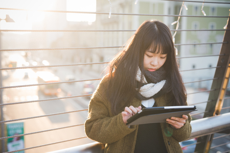 city living: young beautiful asian hipster woman in the city - living town during sunset in backlit - using device wirelles tablet online Stock Photo