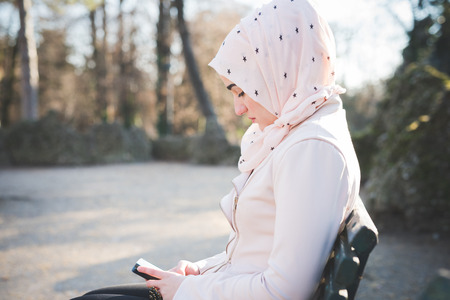 arab spring: young beautiful muslim woman at the park in spring using smartphone connected online wireless